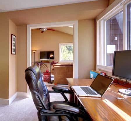 trabajando en casa: Inicio oficina y el ordenador y una silla con paredes de color marrón y la televisión en la sala de estar.