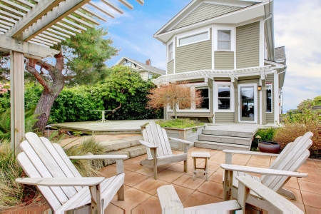 porch: Backyard with white chairs and tall old home during spring. Stock Photo