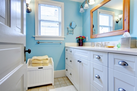 Blue and white bathroom with lots of storage space with open door. Stock Photo