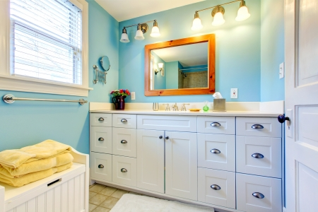 Blue and white bathroom with lots of storage space with open door. photo