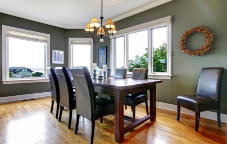 familia cenando: Amplio comedor con sillas de cuero verde y grandes ventanas