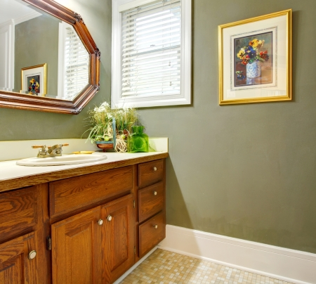 Classic simple green bathroom with wood cabinets and old mirror