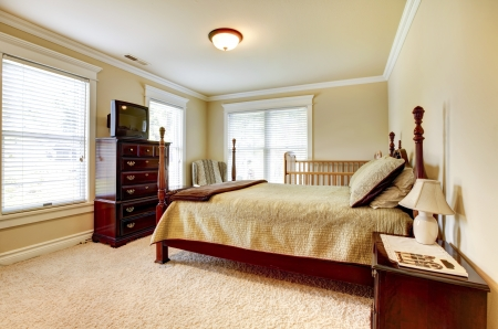 house clean: Large bright bedroom with wood furniture and beige tones.