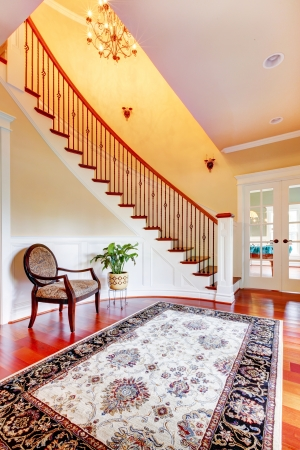 Home interior Entrance with curved staircase and luxury rug with chair. Stock Photo - 17056357