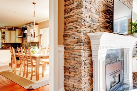 Stone fireplace with tv in theliving room and dining room and kitchen. photo