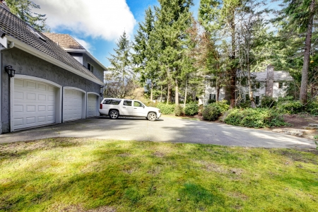 Three car garage and white large car with driveway and pine trees. Stock Photo - 17056362