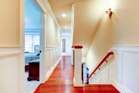 cherry hardwood: Large bright hallway with cherry hardwood and staircase.