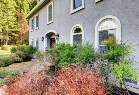 Home exterior of large grey classic house with many narrow windows. Stock Photo - 17056361