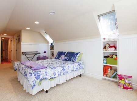 Girl bedroom with attic  vaulted ceiling and beige carpet with toys. Stock Photo