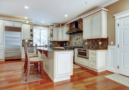 Large white luxury kitchen with cherry hardwood and stone tiles. Stock Photo - 17056388
