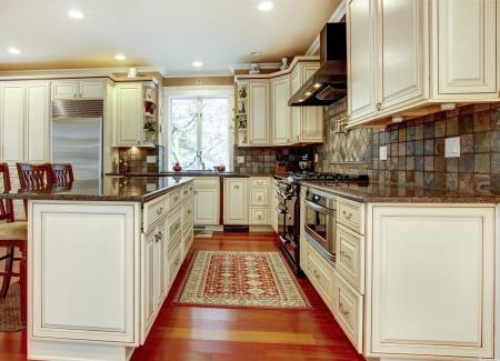 Large luxury white kitchen with cherry hardwood. Stock Photo - 17056389