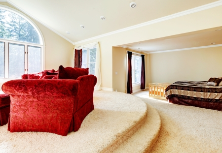 red sofa: Large bright bedroom with red sofa and beige tones.