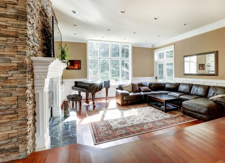Bright luxury living room with stone fireplace and cherry hardwood with leather sofas. photo