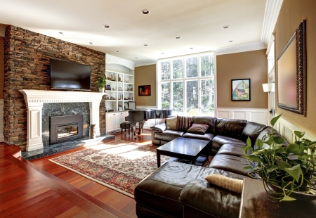 stone fireplace: Luxury living room with stobe fireplace and leather sofas, cherry hardwood and nice rug.