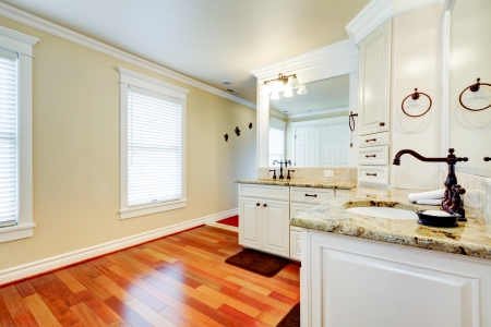 cherry hardwood: Luxury large white master bathroom with cherry hardwood and double  corner sinks. Stock Photo
