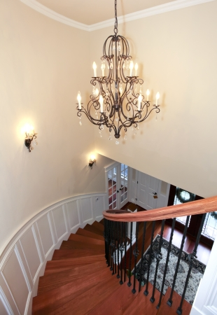 Luxury curved staircase with chandelier, cherry harwood and white trim. photo