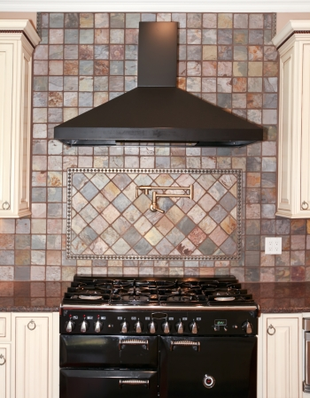stove: Large black kitchen stove with stone tiles and white cabinets. Stock Photo