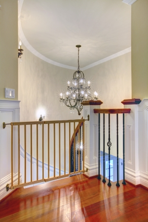 Luxury curved staircase with chandelier, cherry harwood and white trim.Child safety gates. Stock Photo - 17056396