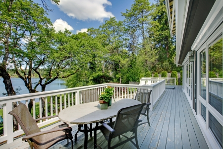 Large long balcony home exterior with table and chairs, lake view. photo