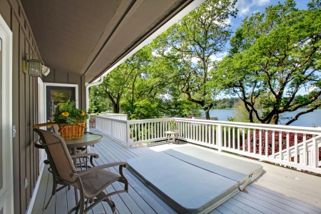 the long lake: Large long balcony home exterior with hot tub and chairs, lake view.