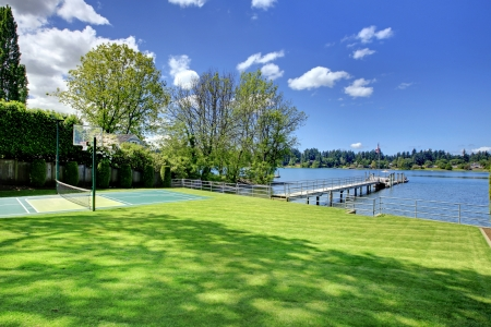 Tennis court with lake and bright green grass. Stock Photo - 17056331