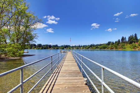 Lake with long wood pier and private party raft. Stock Photo - 17056349