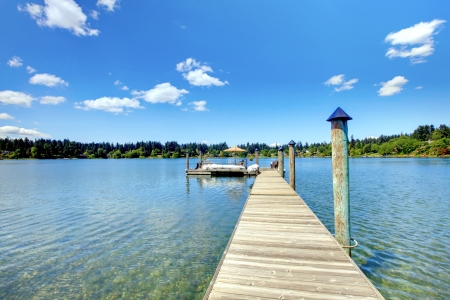 long lake: Lake with long wood pier and private party raft. Stock Photo