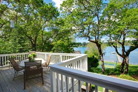 Large balcony home exterior with table and chairs, lake view. photo