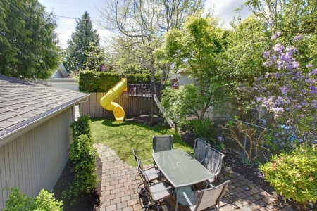 Backyard with kids tree house and table with chairs. photo