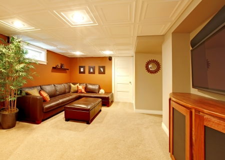 Tv media basement living room with leather sofa. photo
