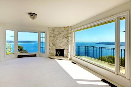 Immobiliën lege slaapkamer met uitzicht op het water en open haard.