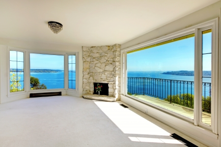 balcony window: Luxury real estate empty bedroom with water view and fireplace.