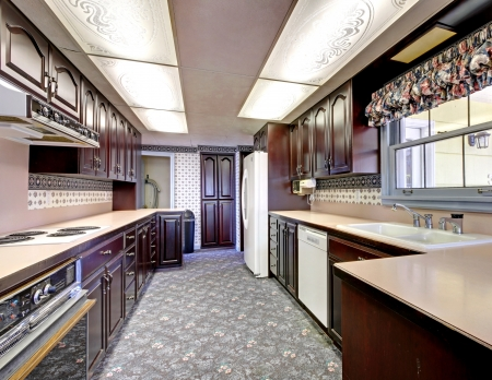 Old wood narrow kitchen with carpet and curtains. Stock Photo - 17100549