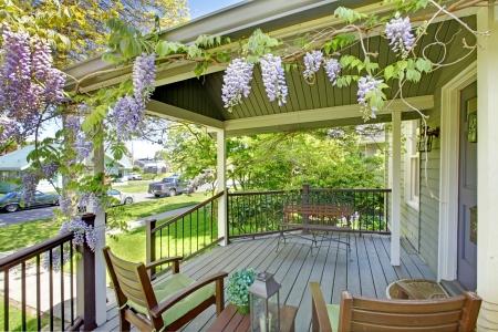 fachada de casa: P�rtico de la casa del frente con sillas y flores.