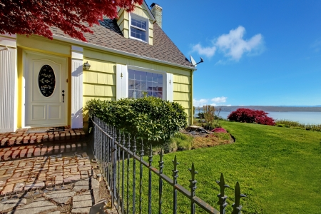 Yellow small clasic home with water view and fence. Stock Photo - 17124885
