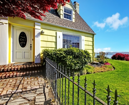 Yellow small home with water view and red maple. Stock Photo - 17124891