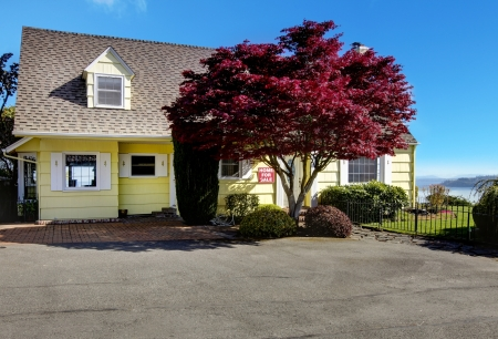 Yellow small home with water view and red maple. Stock Photo - 17124830