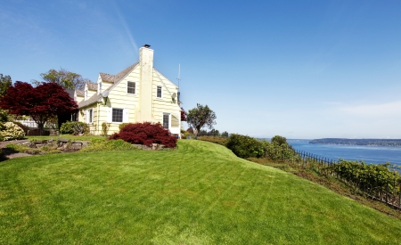 Yellow house on the hill with water view and red maple. Stock Photo - 17124879