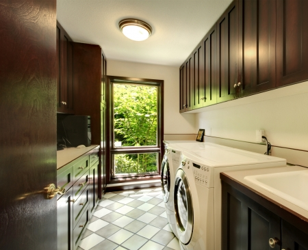 Laundry room with wood cabinets and white washer and dryer. photo