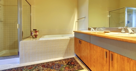 Bathroom with modern wood cabinets, tub and shower with yellow walls. Stock Photo - 17647113