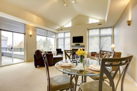 Large bright living and dining room with vaulted ceiling and TV  photo