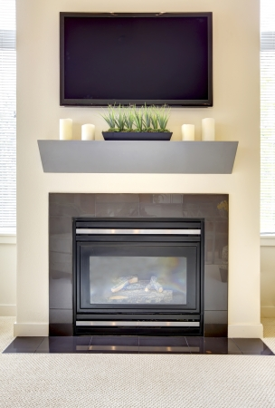 gas fireplace: Modern new fireplace with large TV and shelve with candles  Stock Photo