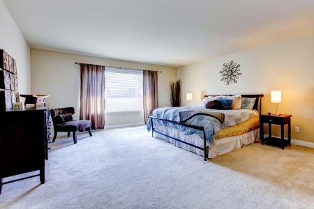 interior designer: Large bedroom interior with beige carpet and black bed.