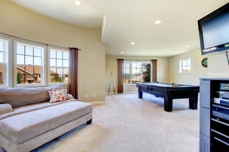 Grande salle familiale avec table de billard, un canapé et une télévision.