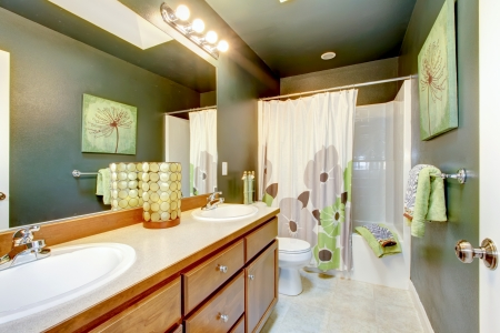 Green bathroom with wood cabinet and shower tub. photo