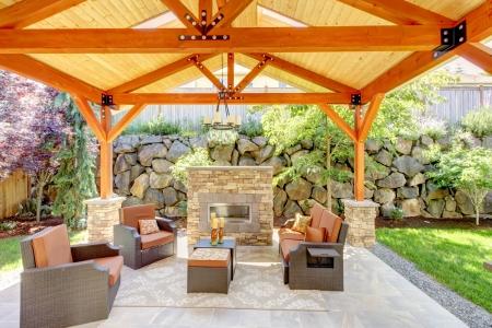Buitenkant overdekt terras met open haard en meubilair. Houten plafond met dakramen. Stockfoto