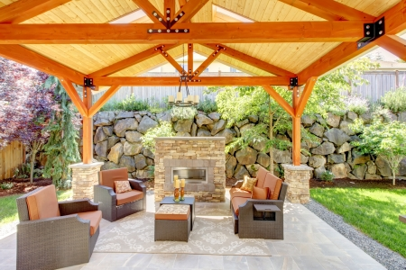 Exterior covered patio with fireplace and furniture. Wood ceiling with skylights. photo