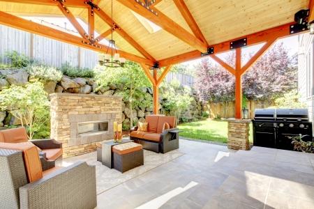 Buitenkant overdekt terras met open haard en meubilair. Houten plafond met dakramen.