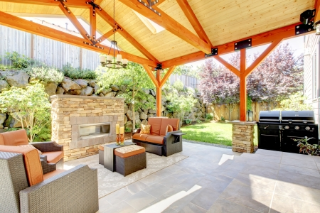 covered: Exterior covered patio with fireplace and furniture. Wood ceiling with skylights.