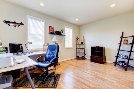 designers interior: Home office interno con pavimento in legno e mobili semplici.